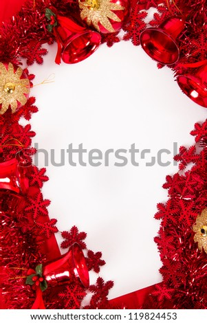 Christmas ornaments, bells, balls, stars and text area on blank paper, sheet on red fabric. - stock photo