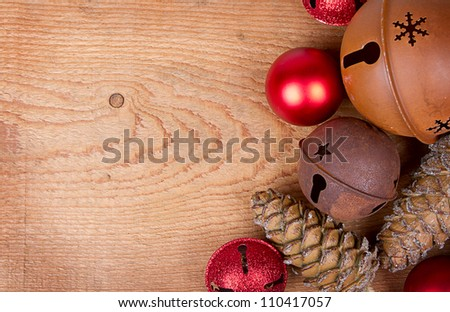 Christmas ornaments pine cones and rusty bells on a brown wood panel - stock photo