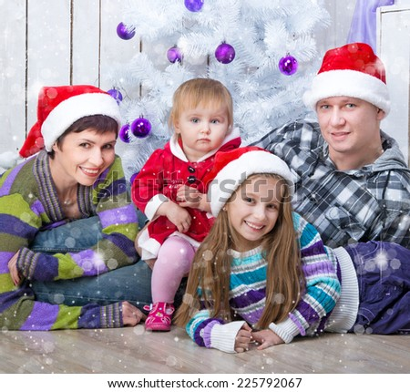 Christmas photo of a family in Santa caps around a decorated Christmas tree - stock photo