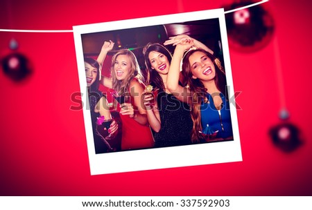 Christmas photograph against pretty friends drinking cocktails together - stock photo