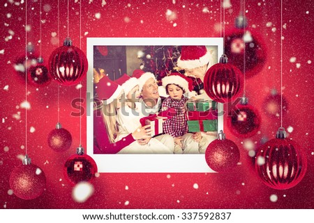 Christmas photographs against family wearing christmas hat while holding presents - stock photo