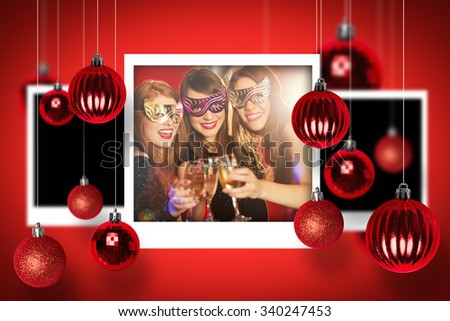Christmas photographs against friends in masquerade masks toasting with champagne - stock photo