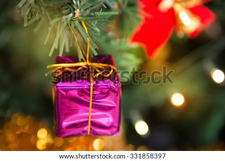 Christmas pink present box baubles on a tree - stock photo