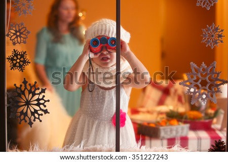 Christmas portrait of little funny girl looking through the window with binoculars, waiting for Santa  - stock photo