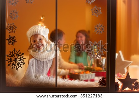 Christmas portrait of little girl looking through the window, waiting for Santa  - stock photo