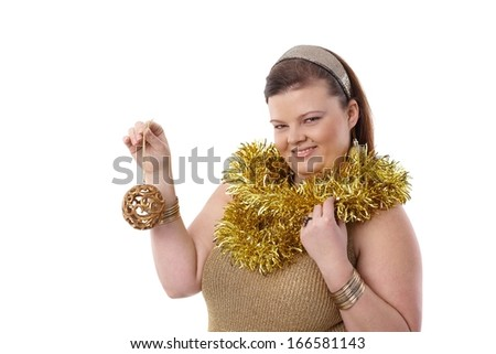 Christmas portrait of overweight woman holding christmas ornaments, smiling. - stock photo