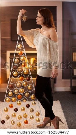 Christmas portrait of pretty woman standing by design tree with star handheld, smiling, daydreaming in cosy living room. - stock photo