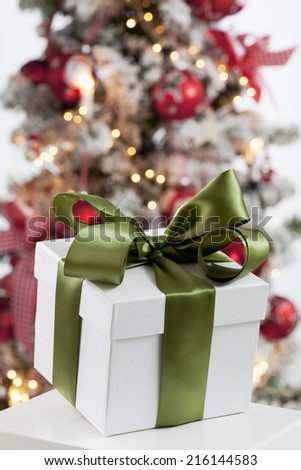 Christmas present close up christmas tree in background - stock photo