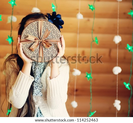 Christmas present in fancy box presented by little girl - stock photo