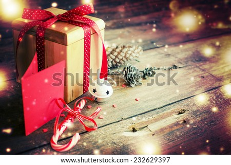 Christmas present with red ribbon on dark wooden background in vintage style / Selective focus - stock photo