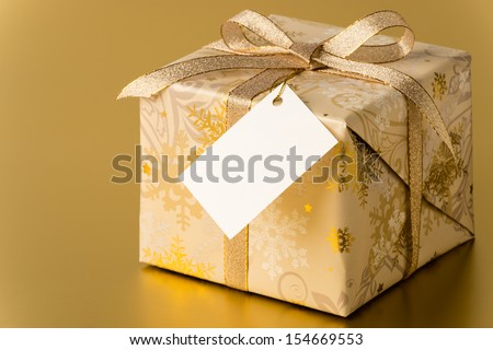 Christmas present with ribbon and blank tag on gold background copyspace - stock photo