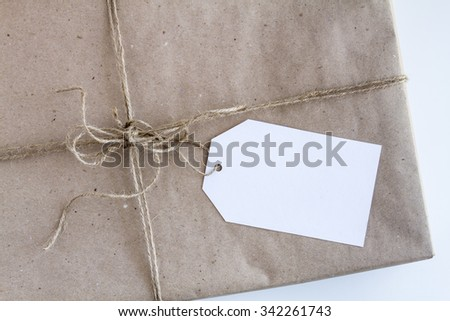Christmas present wrapped in brown wrapping paper with brown burlap twine tied in a bow and blank tag sitting on white background - stock photo
