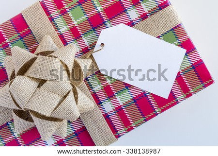 Christmas present wrapped in colorful plaid wrapping paper with brown burlap bow and blank tag sitting on white background - stock photo