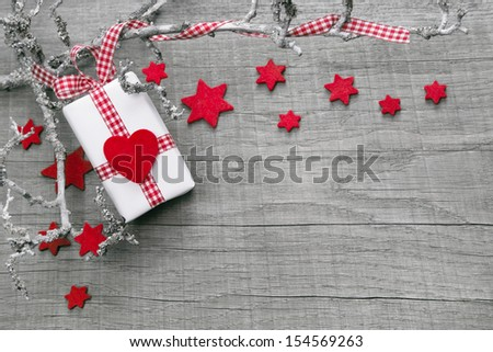 Christmas present wrapped in paper as background with a red heard - stock photo