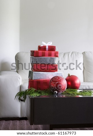 christmas presents and red ornaments on table in modern living room - stock photo