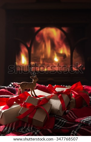 Christmas presents by the fireside  - stock photo