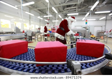 Christmas presents factory.three presents  at production line,two santa clauses workers in the background - stock photo