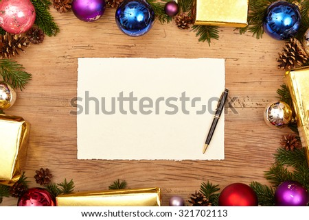 Christmas presents, fir twigs, baubles and blank card with ballpen on wood - stock photo