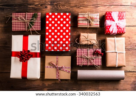 Christmas presents laid on a wooden table background - stock photo