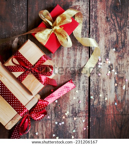 Christmas presents with red ribbon on dark wooden background in vintage style - stock photo