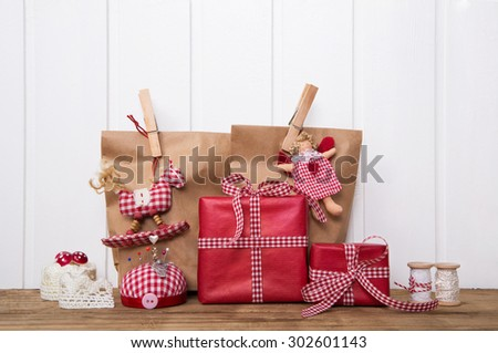 Christmas presents wrapped in paper bags with red white checked ribbon, angel, rocking horse and sewing supplies. - stock photo