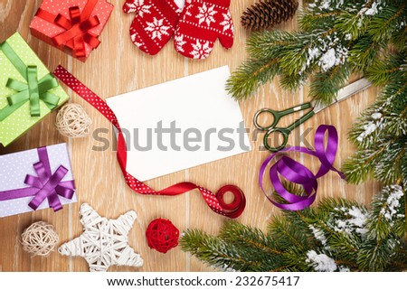 Christmas presents wrapping and snow fir tree over wooden table background with blank card for copy space - stock photo