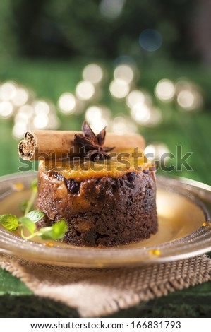Christmas pudding with orange with festive lights - stock photo