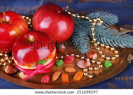 Christmas red apples stuffed with dried fruits on metal tray on color wooden table background - stock photo