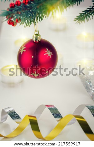christmas red ball hanging on blue fir tree and candle lights defocused background, retro toned  - stock photo