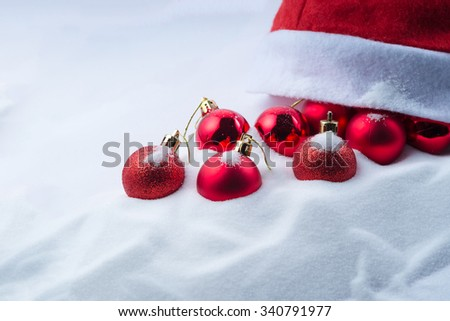 Christmas red balls and red hat decorations on snow - stock photo