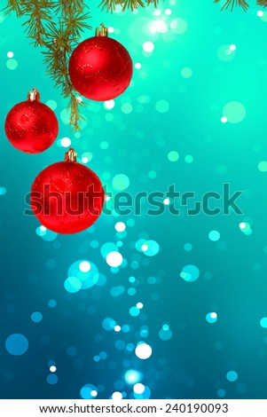 Christmas red balls with green fir tree on colorful blue bokeh background. New Year greeting card. Xmas Decorations. Sparkles and bokeh. Shiny and glowing copyspace, place for text and advert. - stock photo