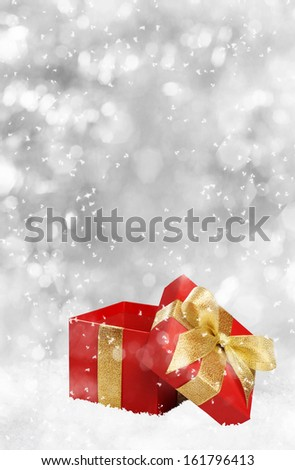 Christmas red gift with golden bow on silver background - stock photo