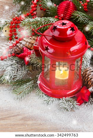 christmas red  glowing lantern   with  evergreen tree and snow on wooden background - stock photo