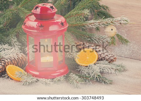christmas red  lantern close up  with decorated evergreen tree and snow, retro toned - stock photo