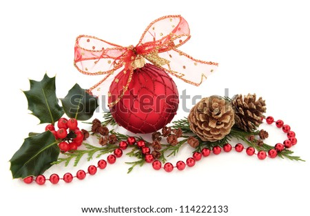 Christmas red sparkling bauble with glitter bow surrounded by holly and cedar leaf sprigs with gold pine cones over white background. - stock photo