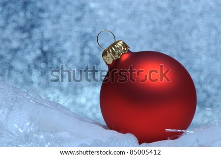 Christmas red sphere. Bokeh background blue toned - stock photo