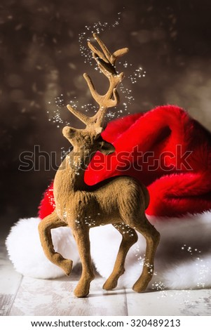Christmas reindeer with santa hat in festive setting - stock photo