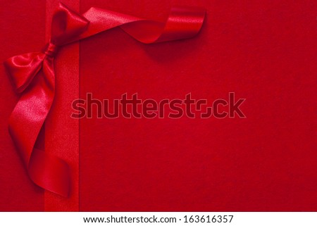 Christmas ribbon with bow on red fabric background - stock photo