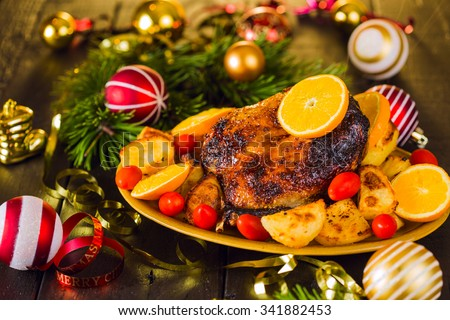 Christmas roast duck served with potatoes, orange and tomatoes on wooden festive decorated table - stock photo