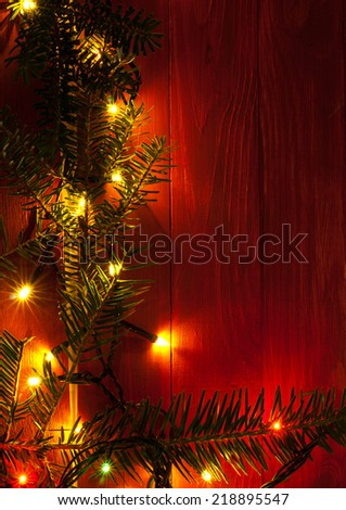 Christmas rustic background - vintage red planked wood with lights and fir twigs and free text space - stock photo