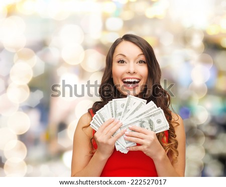 christmas, sale, banking, winning and holidays concept - smiling woman in red dress with us dollar money over lights background - stock photo