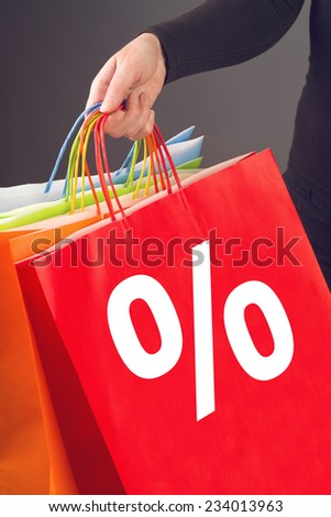 Christmas sale concept, woman holding colorful shopping bags with percentage sign printed on for discount prices seasonal purchasing event. Sale out and clearance sale concept. - stock photo