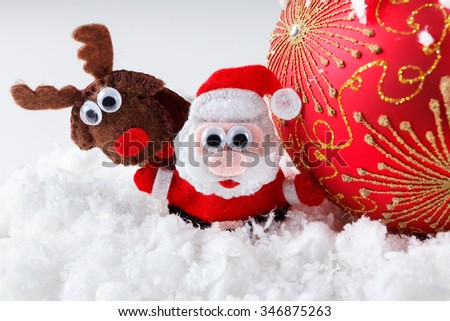 Christmas Santa and reindeer toys on snow with festive New Year balls on a white background - stock photo