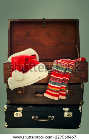 Christmas Santa Claus Caps and Knitting Strips Golfs in Open Wooden Suitcase, toned - stock photo