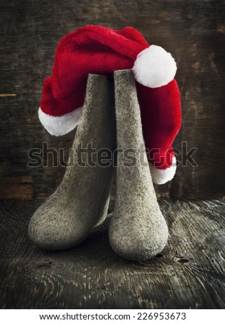 Christmas Santa Claus's hat and felt boots on wooden background. Toned image. - stock photo