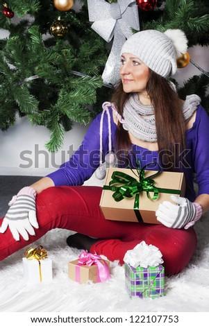Christmas Santa girl holding gifts beside green Christmas Tree - stock photo