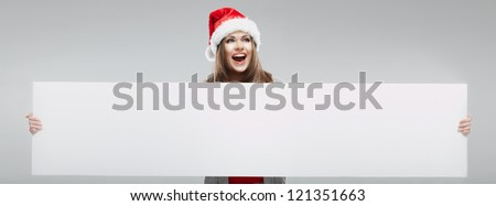 Christmas Santa hat isolated woman portrait. Female smiling model hold white blank board. - stock photo