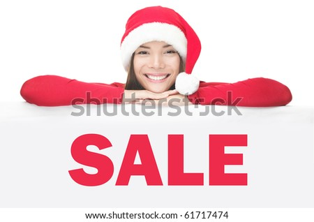 Christmas santa woman smiling cute is showing blank empty billboard sign. Asian Chinese / white Caucasian young female model in red Santa hat. Isolated on white background. Use for Christmas sale or? - stock photo