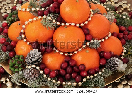 Christmas satsuma orange and cranberry fruit, gold bead decorations, holly, mistletoe and winter greenery over oak background. - stock photo