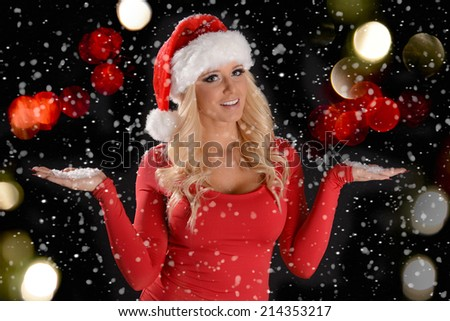Christmas Scene of a pretty young woman wearing Santa hat in the snow - stock photo